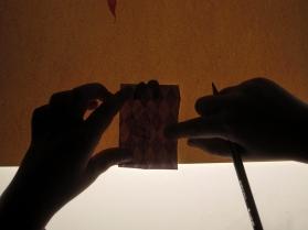 Jimena calcando la silueta del vestido en el papel estampado que quiere utilizar.